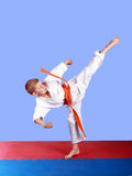 Young athlete with an orange belt beat a circular kick Royalty Free Stock Images