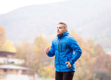 Young athlete in park running in colorful autumn nature. Hipster young athlete in blue jacket running outside in colorful sunny autumn nature. Trail runner Royalty Free Stock Image