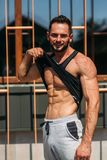 Young athlete posing with a torso for photography on a brick wall background. Bodybuilder, athlete with pumped muscles. Young athlete posing with a torso for Royalty Free Stock Photos