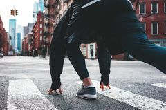 Young athlete preparing to running start. Man runner in start pose on city street. Young athlete preparing to running start royalty free stock photos