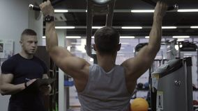 Young athlete is pulling the weight machine in the gym and his male trainer is controlling him. Sportsman has a beautiful arm muscules and is woking on his stock video footage