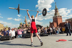 Young athlete in red raises the barbell Stock Image
