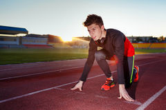 Young athlete runner in a position of readiness to start Stock Photos