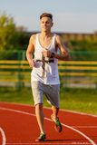 Young athlete running at the running track Royalty Free Stock Image