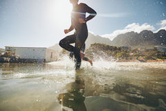 Young athlete running into water Stock Image
