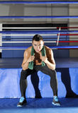 Young athlete sits on edge of ring with green towel. On neck Stock Photography