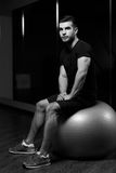 Young athlete sits on fitball stock photo