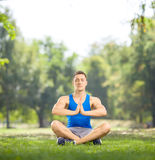 Young athlete sitting on grass and meditating Royalty Free Stock Image