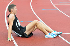 Young athlete sitting on the ground after running race. Tired athlete sitting on the running track after loosing race Royalty Free Stock Image