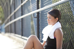 Young athlete sitting resting and thinking. An athletic teenager sitting,resting,and thinking with a serious, worried look Royalty Free Stock Photos