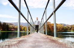 Young athlete with smartphone running in park in autumn. Royalty Free Stock Photography