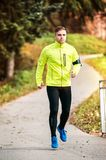 Young athlete with smartphone running in park in autumn. Royalty Free Stock Image