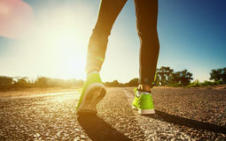 Young athlete in sneakers makes summer morning workout and exercises. Running on the move close-up on a background of the rising sun. Sports and healthy Stock Images