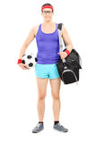 Young athlete with sports bag holding football Royalty Free Stock Images