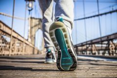 Young athlete sprinter preparing to start a race on Brooklyn Bridge. In New York CIty during summer sunny day stock photography