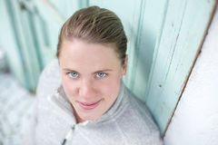 A young athlete stands in front of a turquoise door looking up into the camera Stock Photos