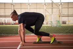 Young athlete at starting position ready to start a race.Sprinter ready for race. A Shot of young athlete at starting position ready to start a race.Sprinter Royalty Free Stock Photo