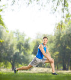 Young athlete stretching his legs in a park Royalty Free Stock Photos
