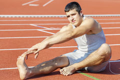 Young athlete stretching on stadium Royalty Free Stock Image