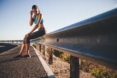 Young athlete taking break from running workout Stock Images