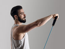 Young athlete in tank top workout with elastic resistance band doing shoulder exercises Stock Images