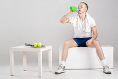 Young athlete with towel drink water after workout on grey background. Young athlete with a towel drink water after a workout on a grey background Royalty Free Stock Photography