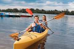 Young athlete training beautiful woman in kayak Royalty Free Stock Images