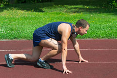 Young athlete on the training track. The young man is engaged in run on the track Stock Image