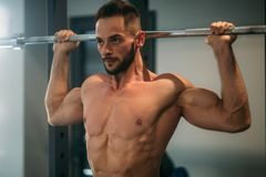 A young athlete trains in the gym. Shows the muscles of the back and chest Stock Photo