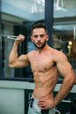 A young athlete trains in the gym. Shows the muscles of the back and chest Royalty Free Stock Images