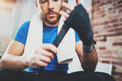 Young athlete tying black boxing bandages.Boxer man concentrating before kickboxing training. Blurred background Stock Image