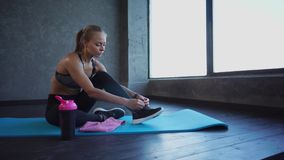 Young athlete tying shoelaces on sneakers, a lady is sitting on a rug for yoga. A young and attractive sportswoman ties up shoelaces on sneakers, a woman takes stock footage