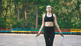 Young Athlete Woman in Comfortable Sport Outfit Jumping Rope on a Sports Field in the Park stock footage