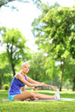 Young athlete woman sitting on a mat and stretching in a park Stock Image