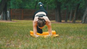 Young Athlete Woman in Sport Outfit Engaged Fitness Lying on a Carpet in a Park on a Green Lawn stock footage
