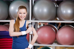 Young athlete woman in sportswear holds a water bottle Stock Image