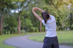 Young athlete woman streching in the park outdoor, female runner warm up ready for jogging on the road outside, asian Fitness walk royalty free stock image
