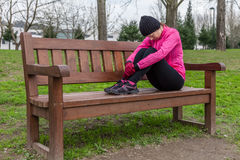 Young athlete woman tired or depressed resting on a bench Royalty Free Stock Image