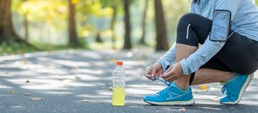 Young athlete woman tying running shoes in the park outdoor, female runner ready for jogging on the road outside, asian Fitness wa stock photo
