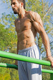 Young Athlete Working Out in an Outdoor Gym. Street Workout Exercises. Tense Muscles. Young Athlete Working Out in an Outdoor Gym. Street Workout Exercises Royalty Free Stock Images