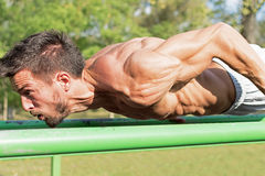 Young Athlete Working Out in an Outdoor Gym. Street Workout Exercises. Tense Muscles. Young Athlete Working Out in an Outdoor Gym. Street Workout Exercises Stock Photo