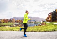 Young athlete running in park in colorful autumn nature. Young athlete in yellow jacket running outside by the lake. Trail runner training for cross country Royalty Free Stock Photos