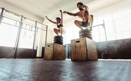 Fitness couple doing a box squat at the gym. Young athletes box jumping at cross training gym. Fitness men and women doing a box squat at the gym. Fitness stock image