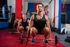 Young athletes crouching with barbells Royalty Free Stock Photos