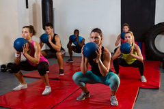 Young athletes crouching with exercise balls Royalty Free Stock Photography