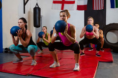 Young athletes crouching with exercise balls on mats. At fitness studio Stock Image