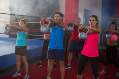 Young athletes exercising with kettles by boxing ring royalty free stock image