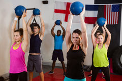 Young athletes holding exercise balls with arms raised Stock Photography
