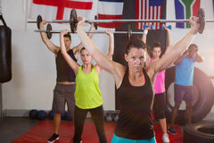 Young athletes lifting barbells against flags Stock Photo