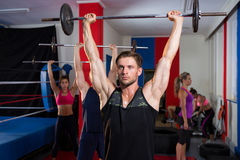 Young athletes lifting barbells with arms raised Stock Photos